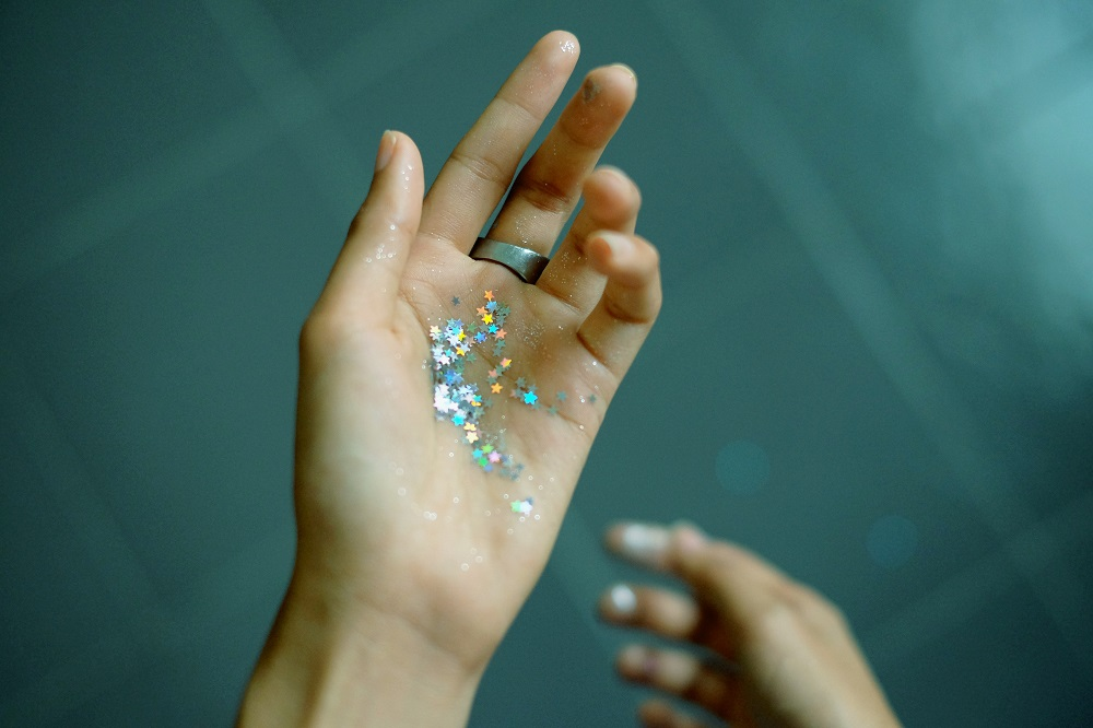 A hand full of glitter sequins shining. Image taken by Mink Mingle, a talented Thai photographer.
