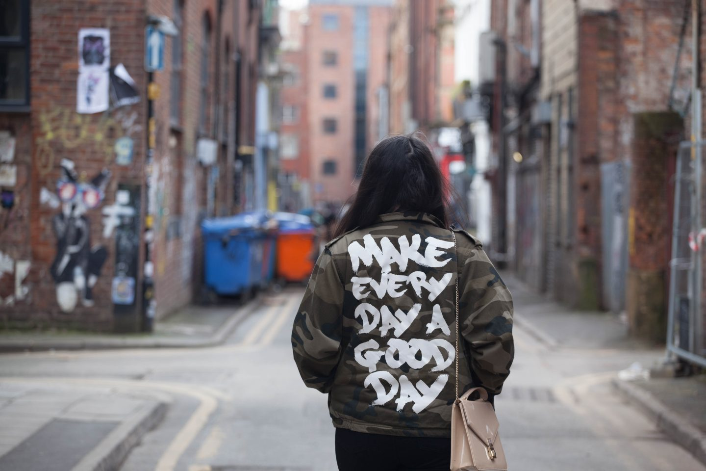Image Shows: Shot of Jess Wilby from Philocalist walking down a Manchester backstreet wearing a camo jacket that displays the message 'Make every day a good day'.