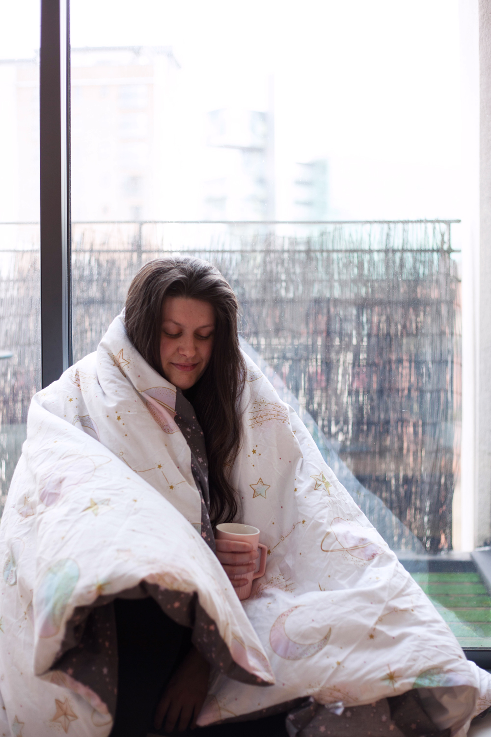 Image shows a sleepy woman (Jess Wilby) wrapped in her duvet in front of a city backdrop, with a cup of tea.