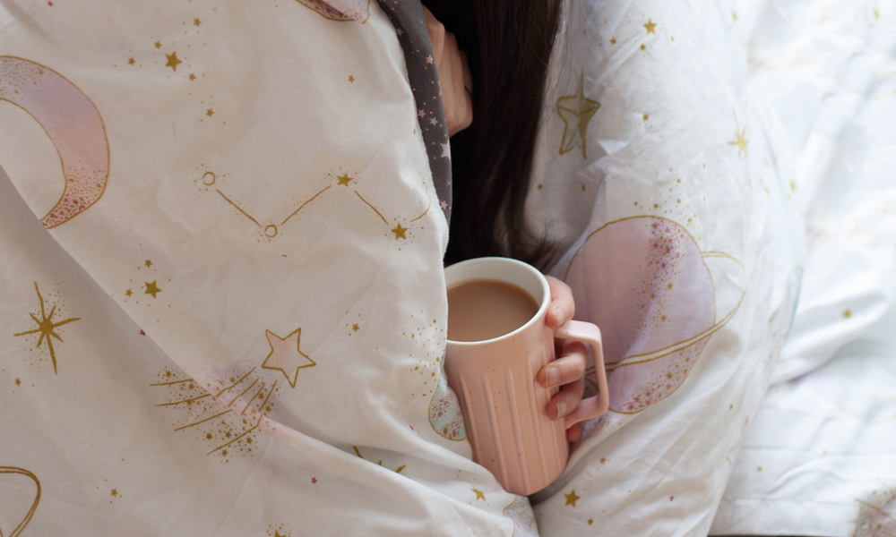 Image shows a close up shot of someone with a cup of tea hiding under a duvet cover.